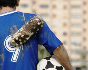 April 2004 --- Soccer Player Carrying Muddy Shoes --- Image by ? Royalty-Free/Corbis