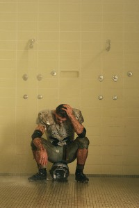 Dejected Football Player Sitting in the Showers