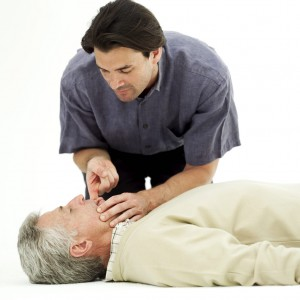 Young Man Clearing an Elderly Man's Airway